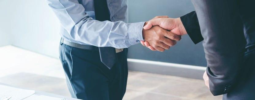 Duas pessoas se cumprimentado após fechar um novo contrato de negócios.
