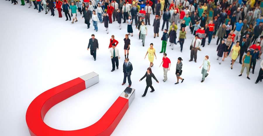 Muitas pessoas sendo atraídas para um imã, fazendo relação as técnicas como o inbound sales.